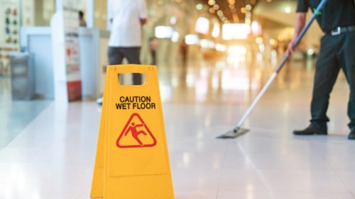 Worker Mopping Floor With Wet Floor Caution Sign On Floor
