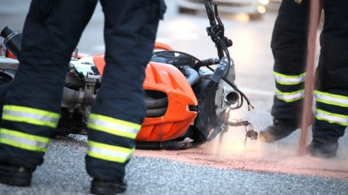 Emergency worker standing in front of crashed motorcycle