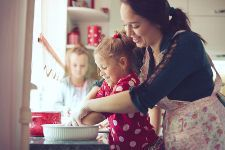 Stock photo of a mother cooking in the kitchen with her small daughters.