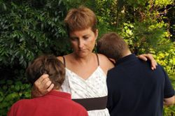 Stock photo of a mother comforting her two teenage sons following the death of a loved one.