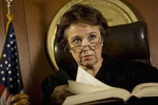 Stock photo of an elderly female judge sitting on the bench in a courtroom.
