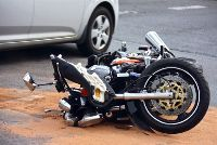 Stock photo of a damaged motorcycle laying on a city street following an accident with a car.