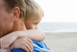 Stock photo of a young boy hugging his father in front of the ocean.
