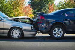 Stock photo of a rear-end car accident between a silver car and a black car.