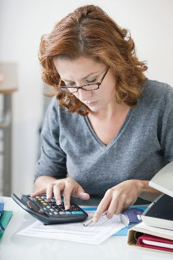 Stock photo of a woman examining legal documents and using a calculator.