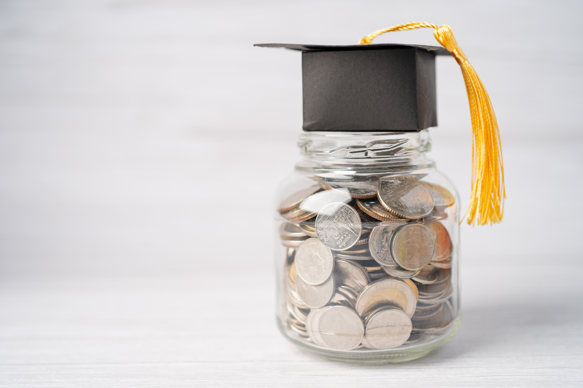 A graduation cap sitting on a jar of quarters.