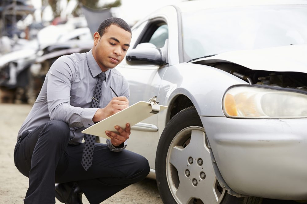 An insurance adjuster taking notes about the damage to a car after an accident.